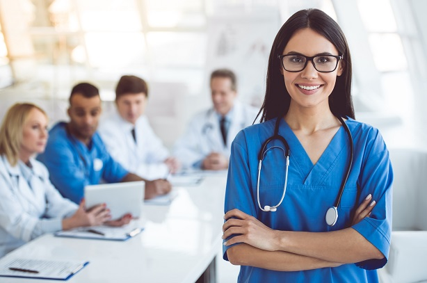 Beautiful young female medical doctor is looking at camera and smiling while her colleagues are sitting in the background